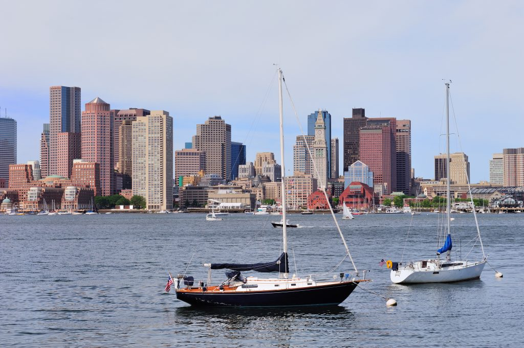 Sailing boat rest and Boston downtown skyline with urban skyscra